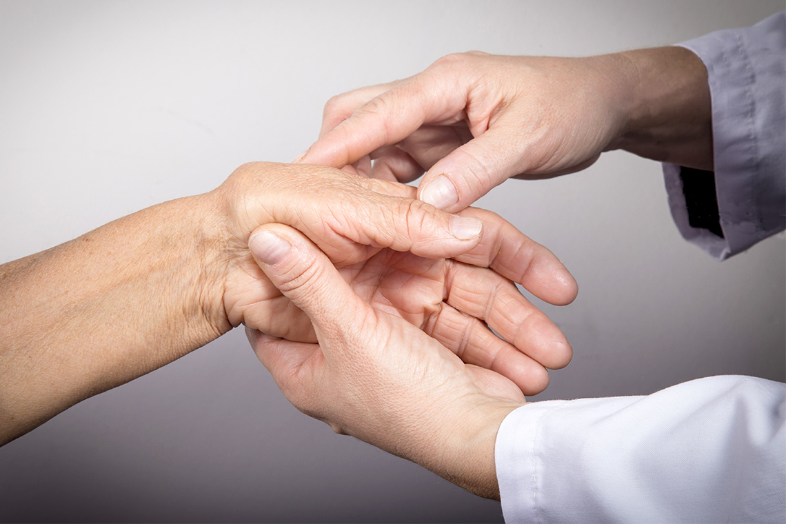 photo of a doctor examining a patient's hands