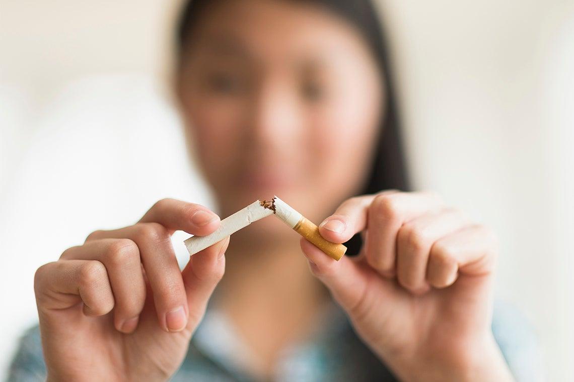 Asian woman breaking a cigarette in half