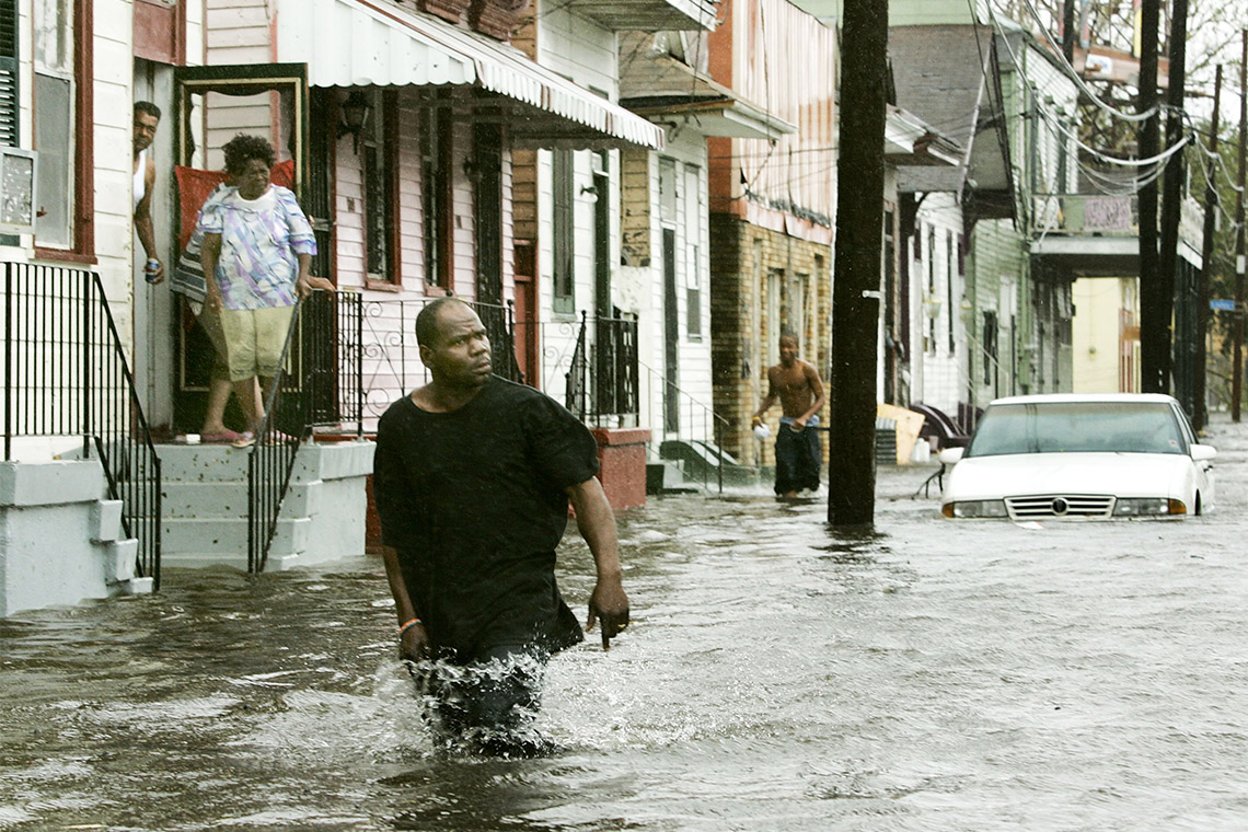 A man walks down a flooded street in New Orleans after Hurricane Katrina