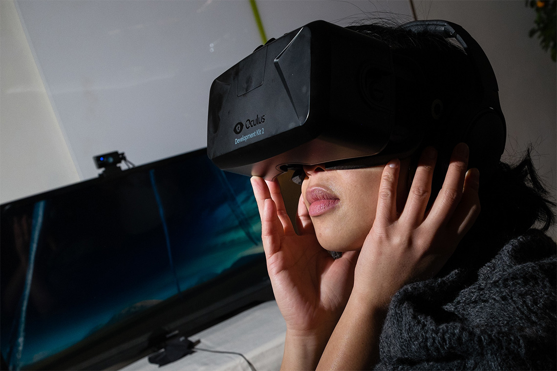 a southeast asian woman wears an oculus headset in a darkened room