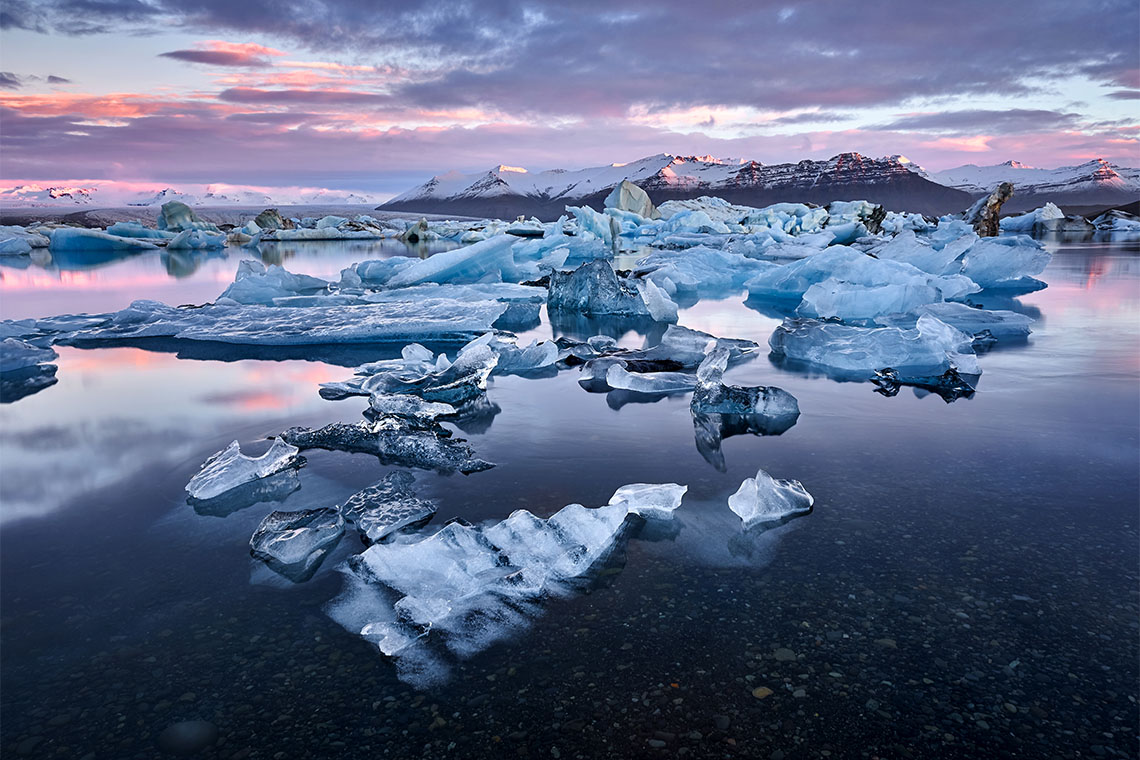 Sun sets over multiple small icebergs