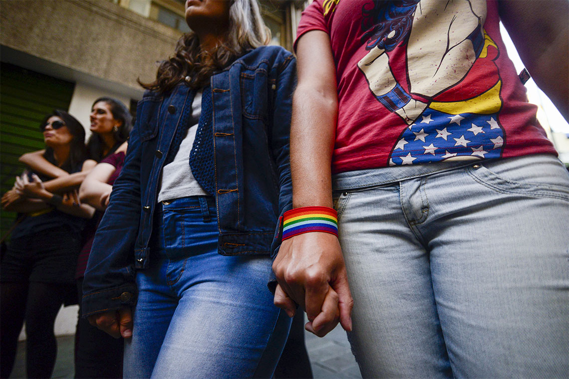 a row of 4 women hold hands as they march in a LBGT parage in Sao Paulo Brazil