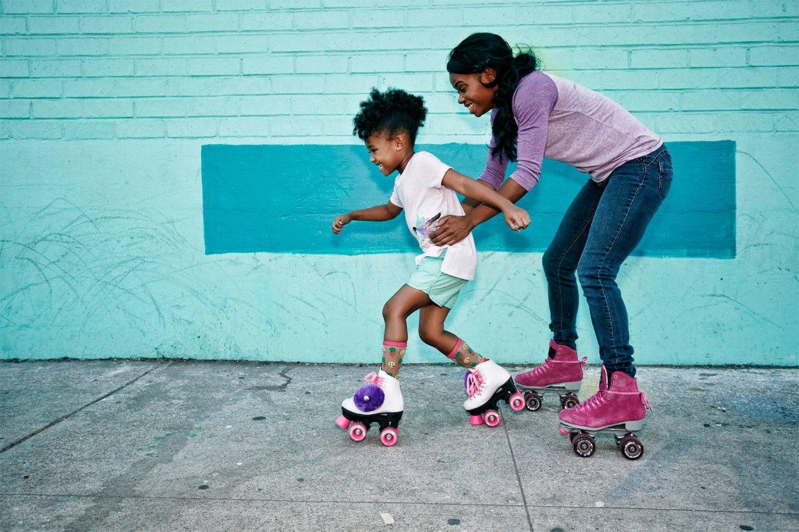 mother helps daughter roller skate