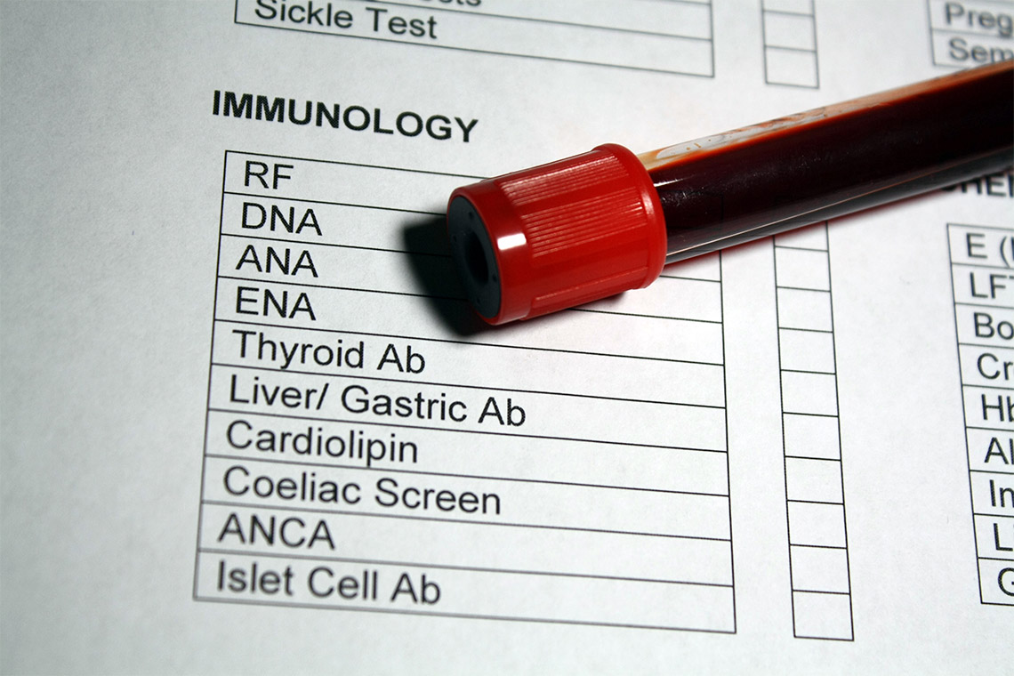 Vial of blood rests on a blood test requisition form