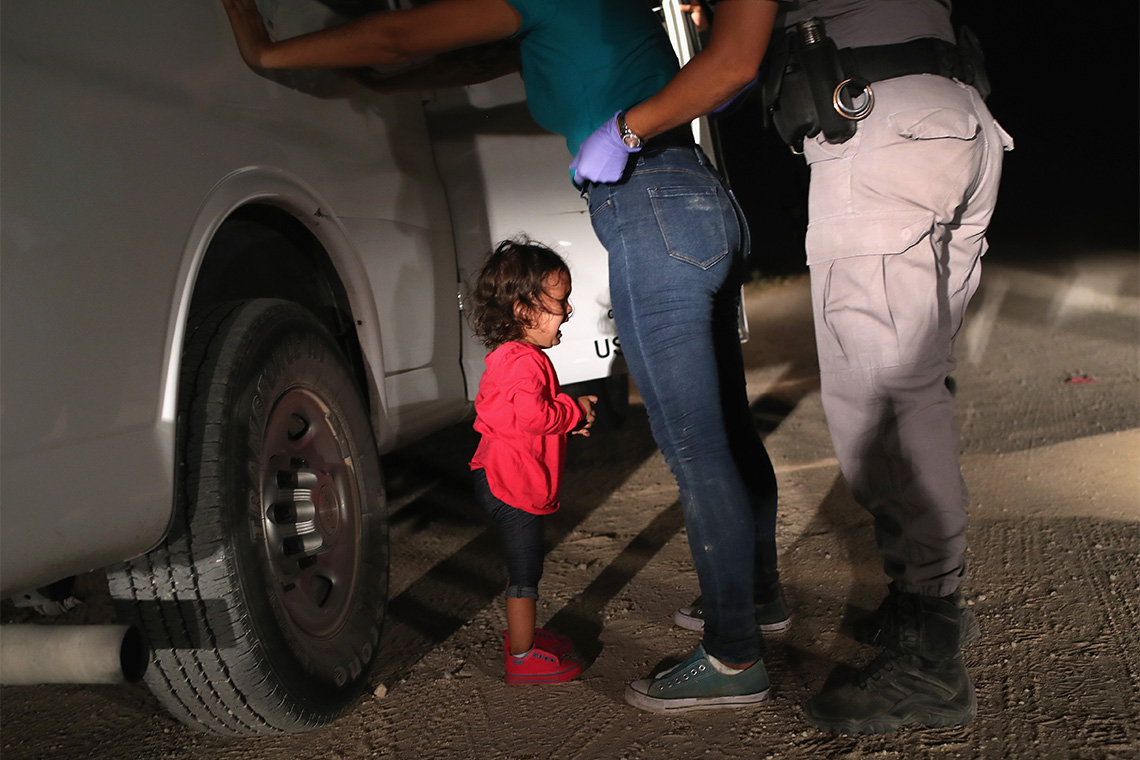 A young girl in a red sweater cries beside a white truck at night near the border while a border patrol officer detains her mother