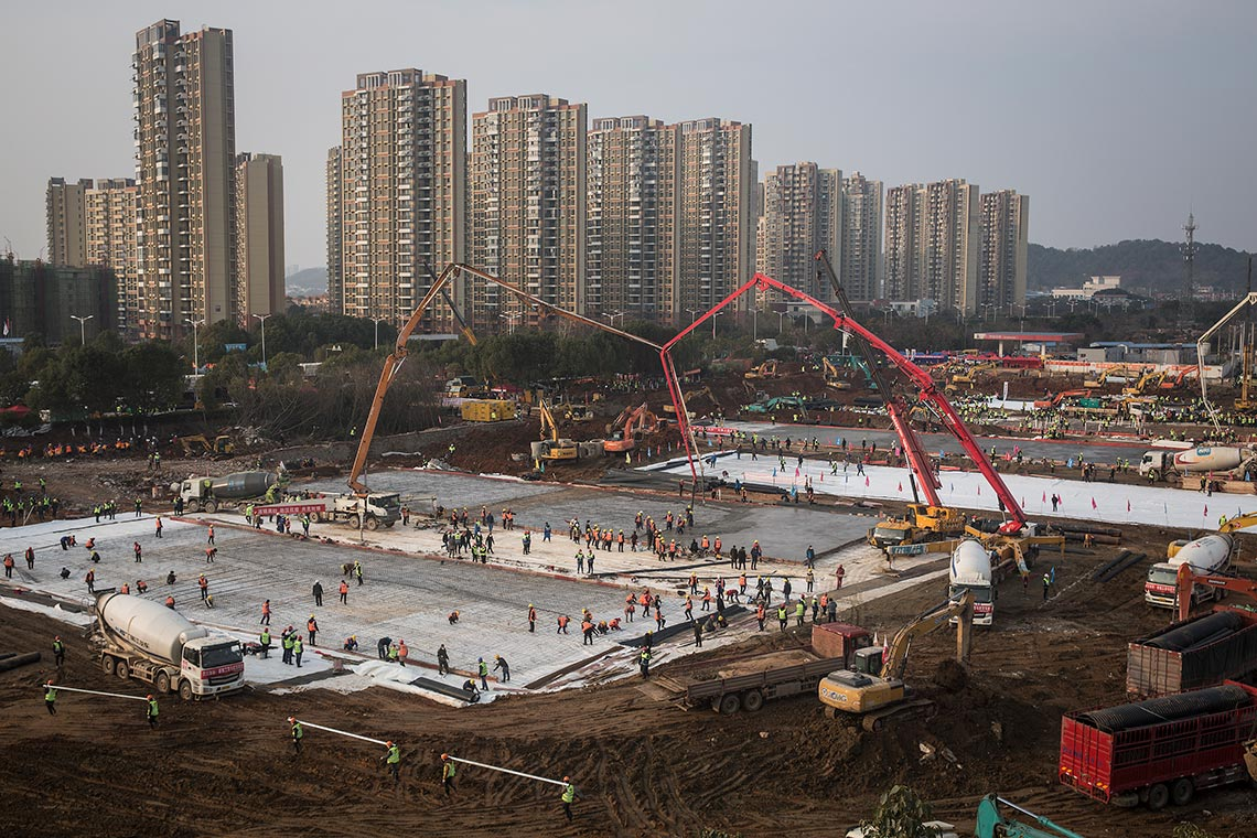 Photo of cranes and construction workers at the site of two new hospitals in Wuhan, China