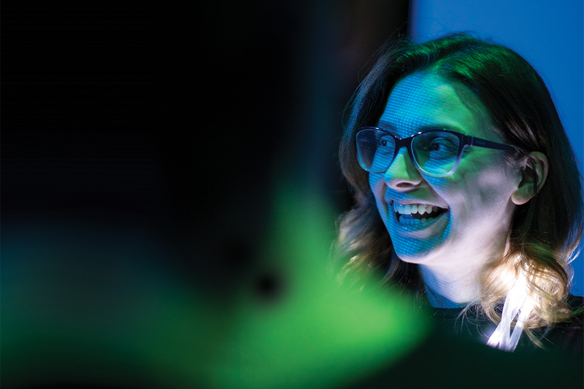 A caucasian woman wearing glasses in a darkened room with a digital projection on her face
