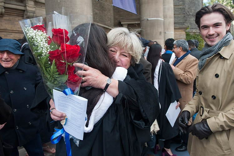 Family hugging outside Convocation Hall