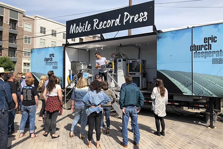 People stand outside one of Viryl Technologies mobile record presses that fits inside a shipping container