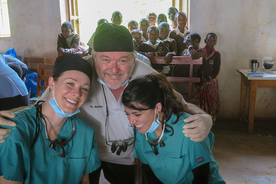 Izchak Barzilay laughing with dentistry students in Uganda as locals look on in the background