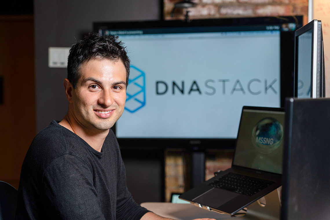 Marc Fiume sits at a computer, a monitor displaying the DNAstack logo is in the backbround