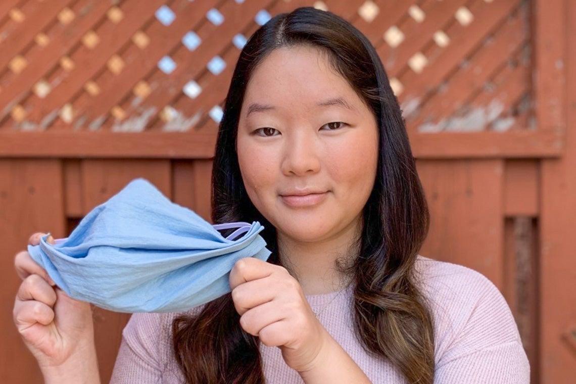 Portrait of Calandra Li holding up a homemade mask