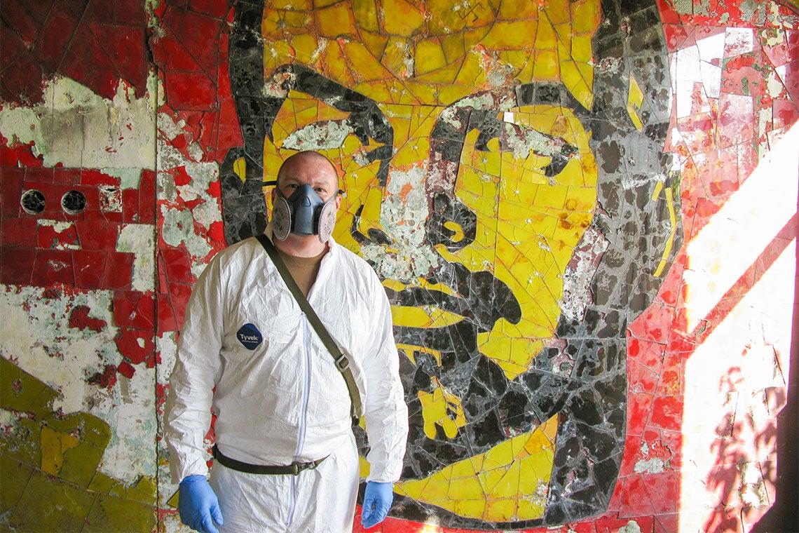 Gary Johnston in a tyvek suit in front of a graffti art rendition of Lenin