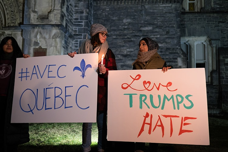 Mourners hold up Love Trumps Hate sign at vigil for victims of Quebec City mosque shooting