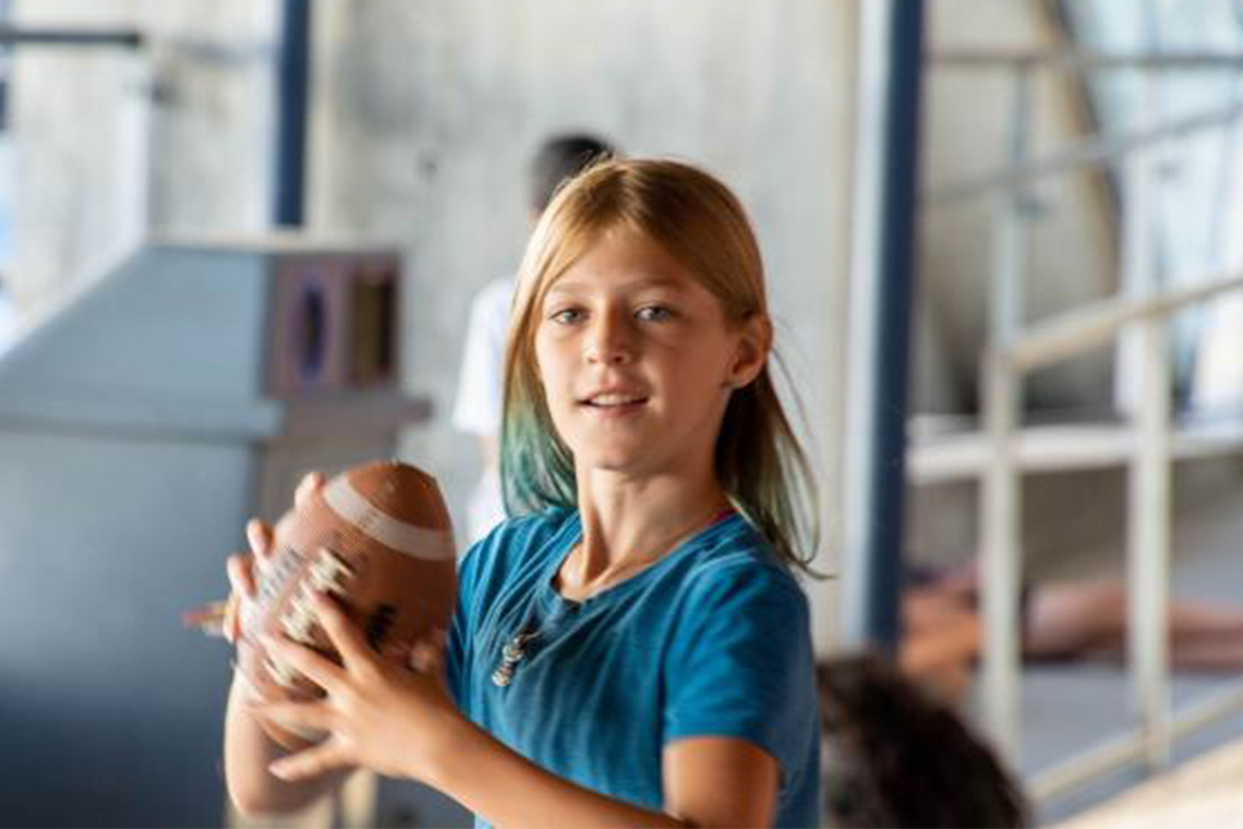 young girl catches a football