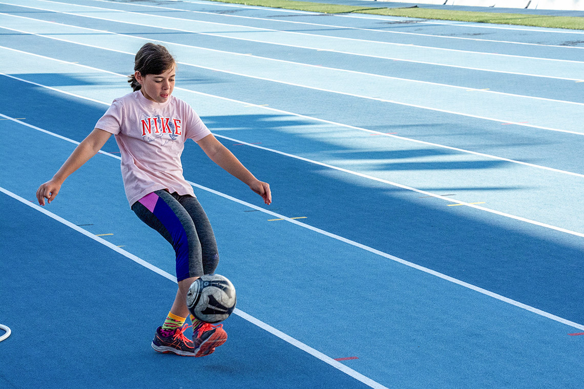 Young girl practices with a soccer ball at the university of toronto