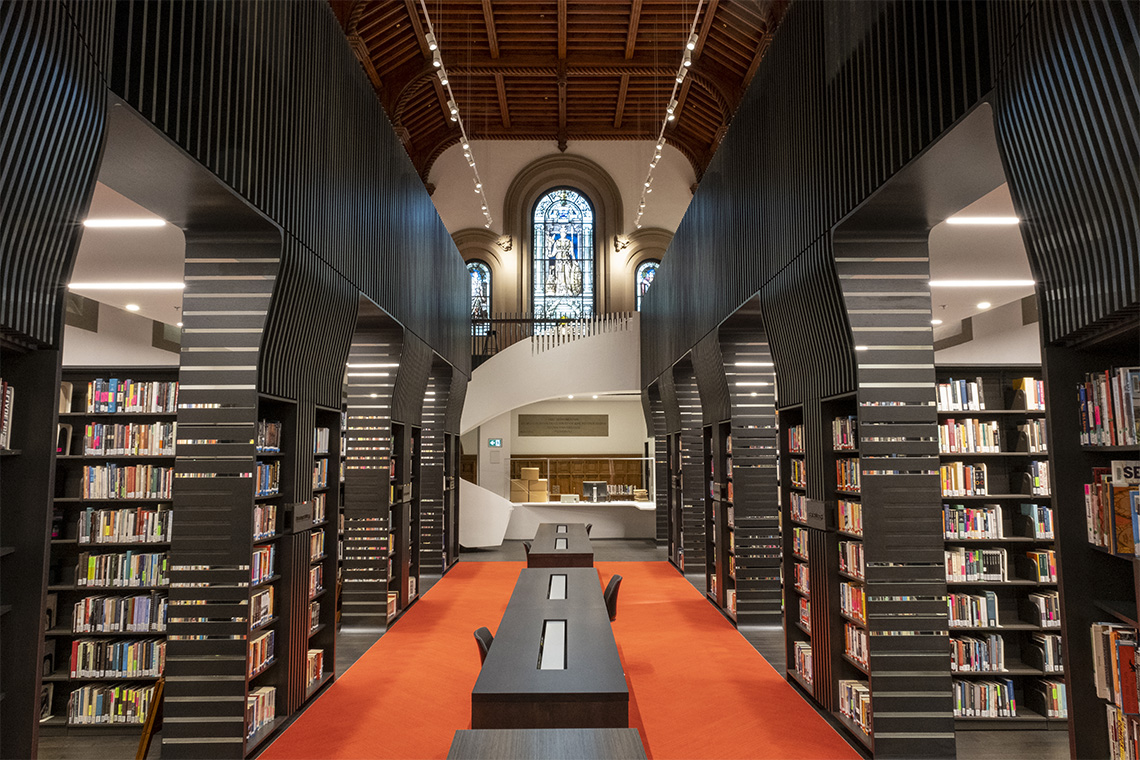 A view of the newly renovated library at University College with spiral staircase and stained glass window in the background