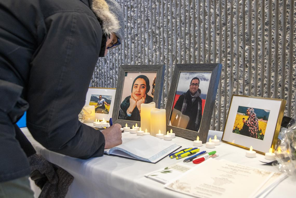 Mourner signs a book of condolences at a vigil for the victims of Flight 752