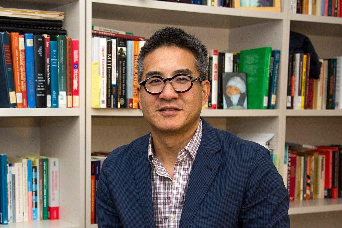 Portrait of Joe Wong in front of a bookshelf