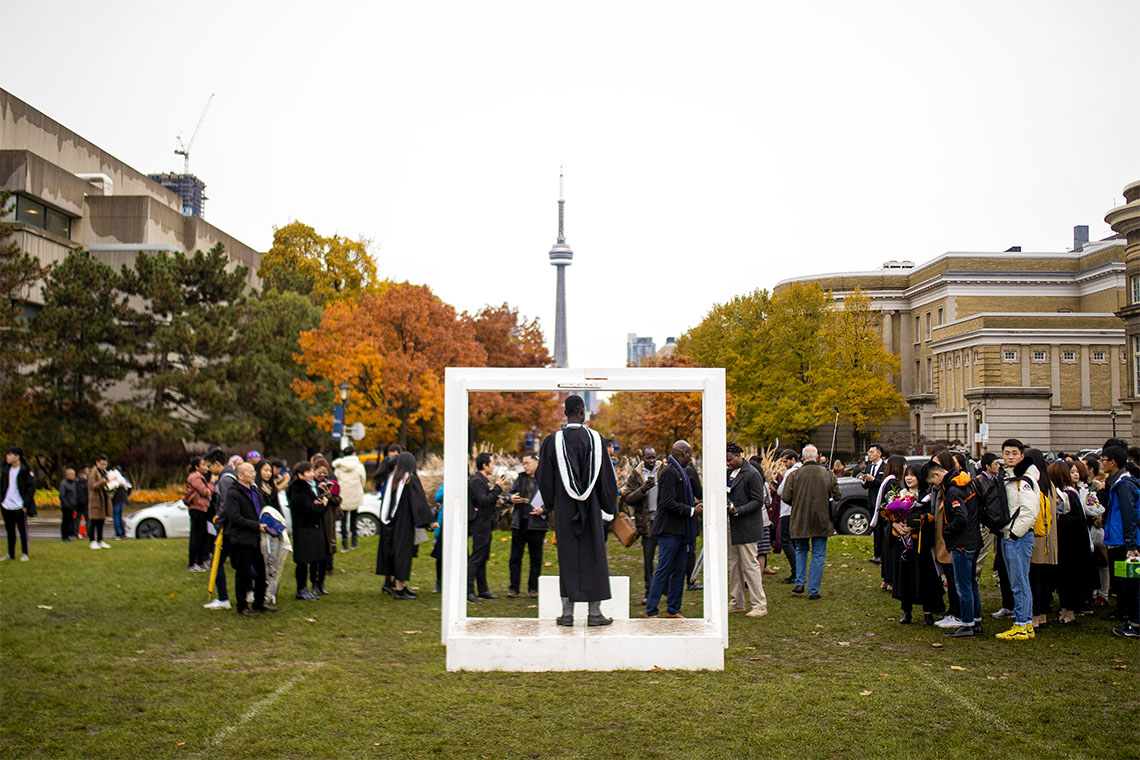 A person is posing in a large photo frame with the CN Tower is in the background