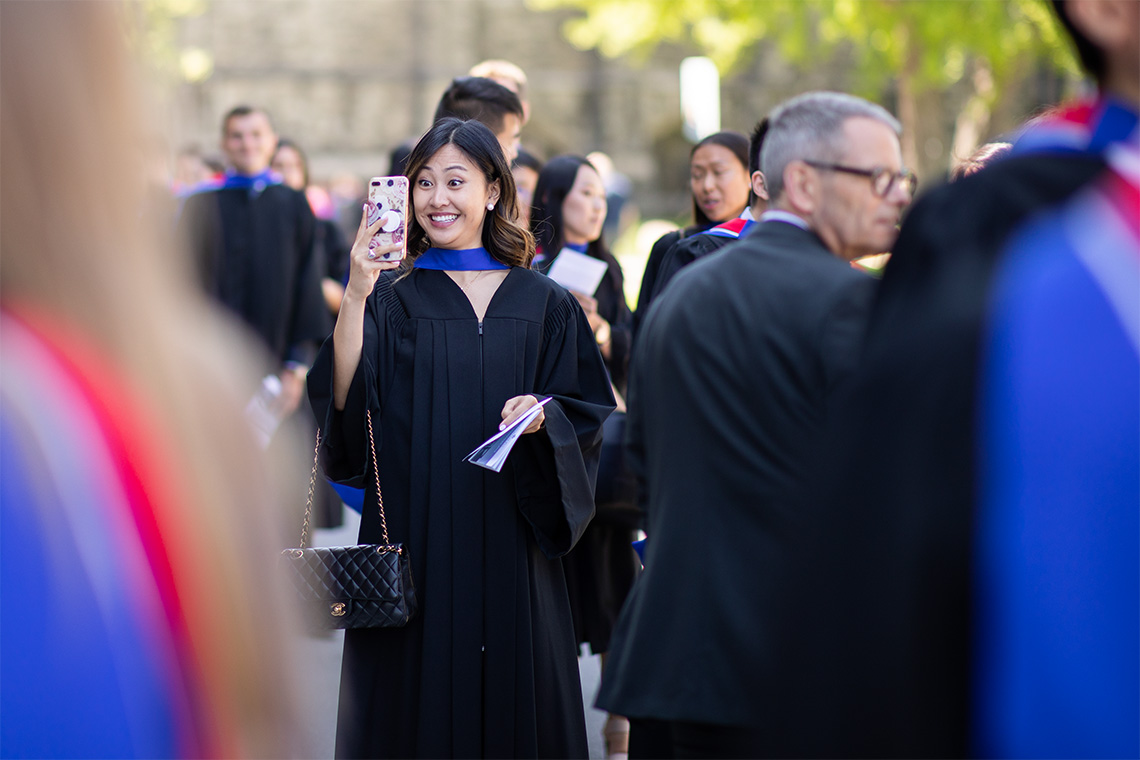 A woman in her graduation gown take a selfie just outside of convocation hall