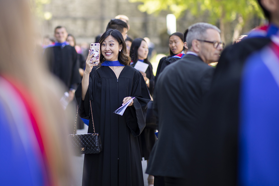 A female graduate takes a selfie outside of convocation hall