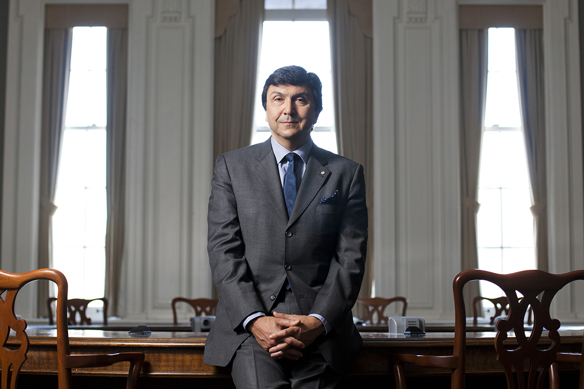 portrait of David Naylor leaning against a large table at Simcoe Hall