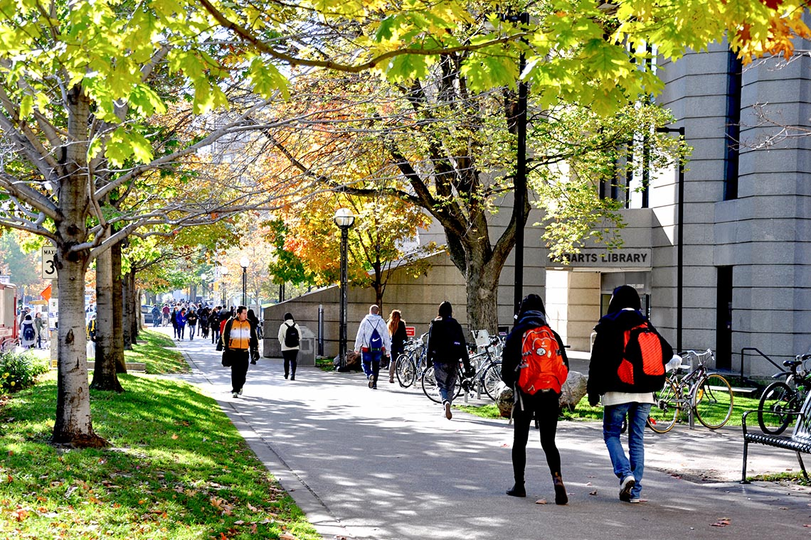 Students walking past robarts library from north to south surrounded by green foliage