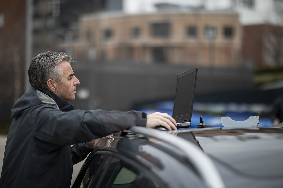 Nicholas Hoban uses a laptop on top of his car