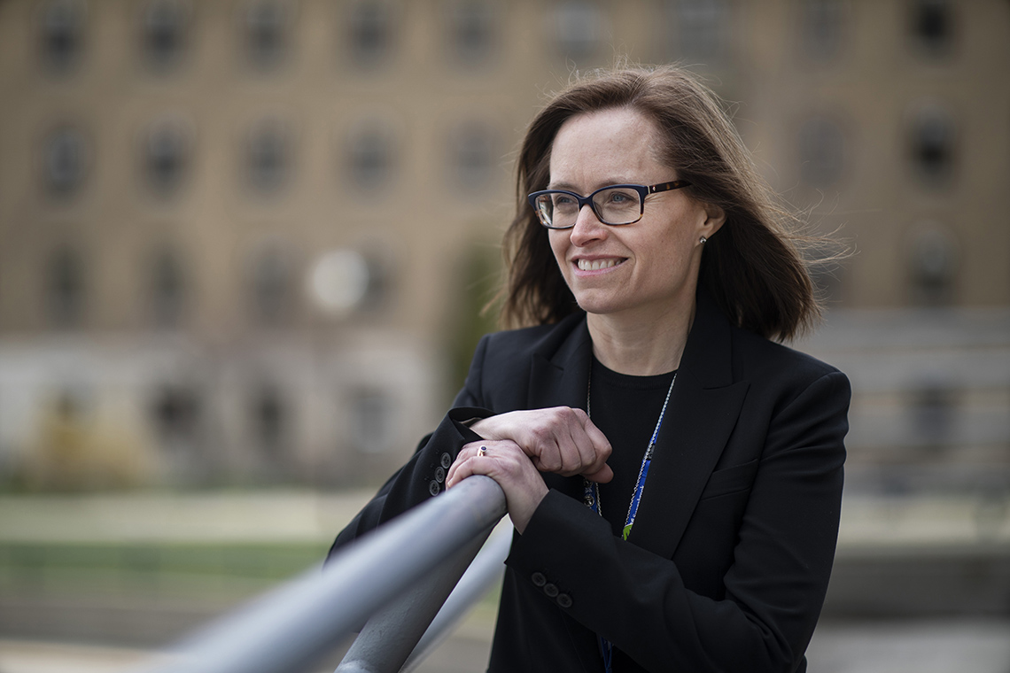 Photo of Jeannie Callum of U of T and Sunnybrook as she leans on a railing with a building in the background