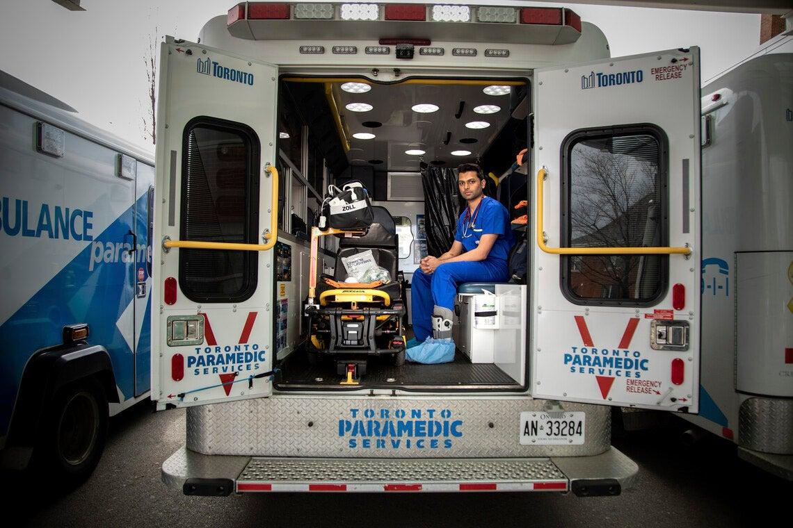Sameer Masood sits inside an ambulance