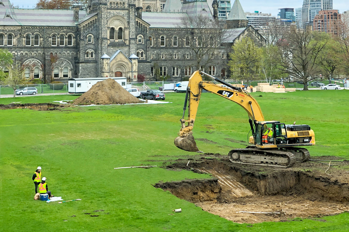 A backhoe digs a pit on Front Campus, with workers looking on and University College in the background