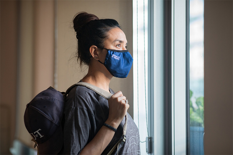 Woman wearing a u of t branded mask indoors