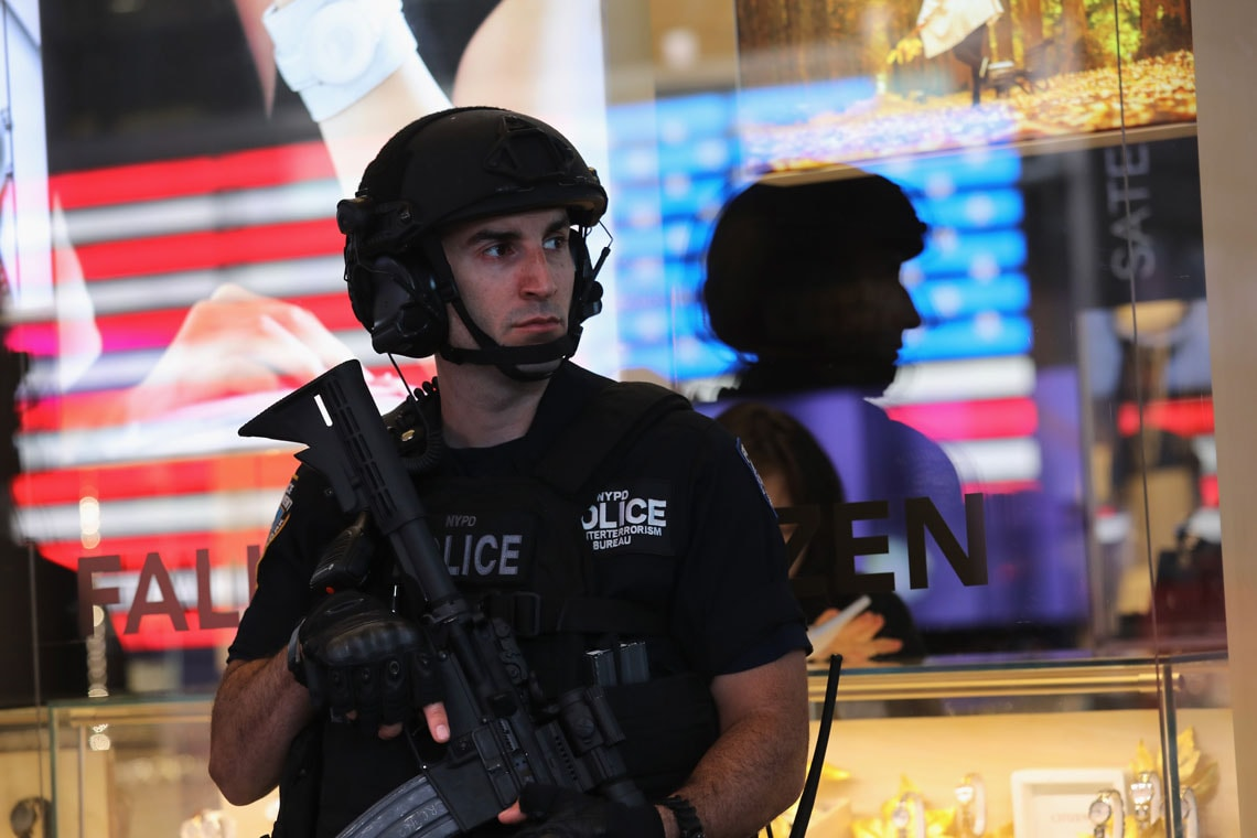 Heavily armed policeman stands on guard in Times Square