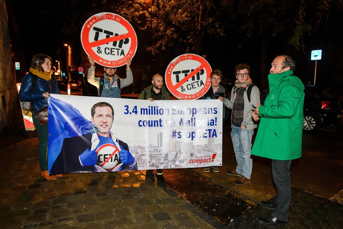 Protesters hold up a placard reading '3.4 million Europeans count on Wallonia - stop CETA' as a meeting on CETA takes place at the Walloon parliament in Namur, Belgium