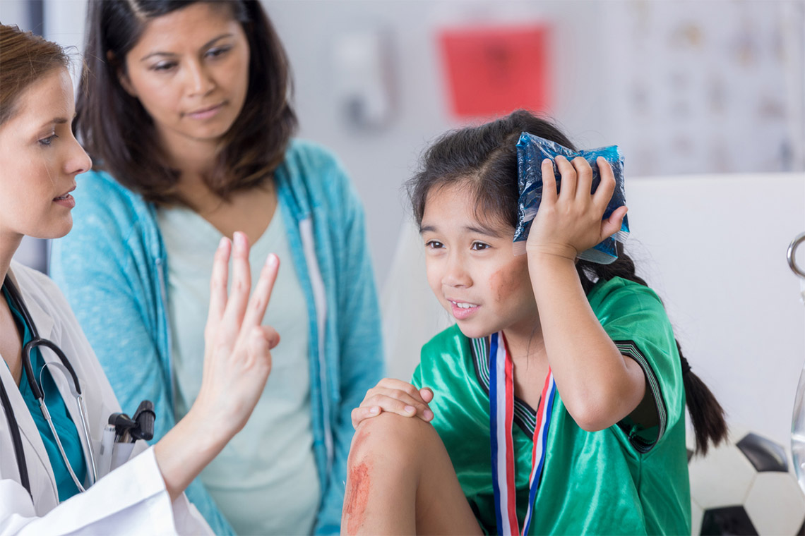 A young girl holds an ice pack to her head while a doctor asks her how many fingers she's holding up