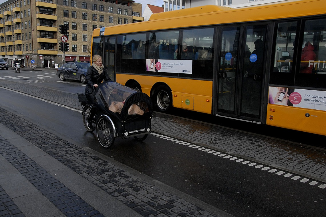 A female cyclist and a bus in Copenhagen