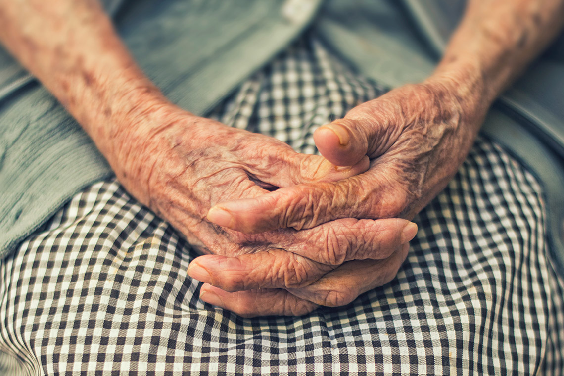 an elderly woman clasps her hands together on her lap