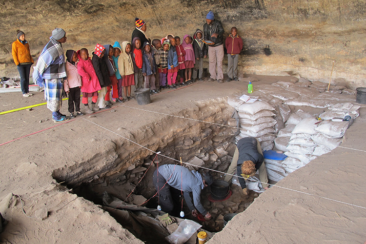 Children look at archaeologists at work