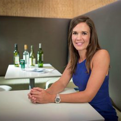 portrait of erin hobin seated at a restaurant table with bottles of wine in the background