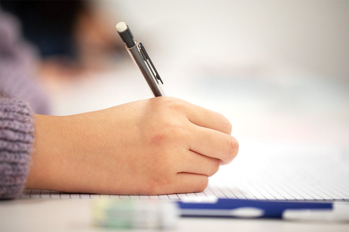 A close of up a student's hand holding a pencil as they write an exam