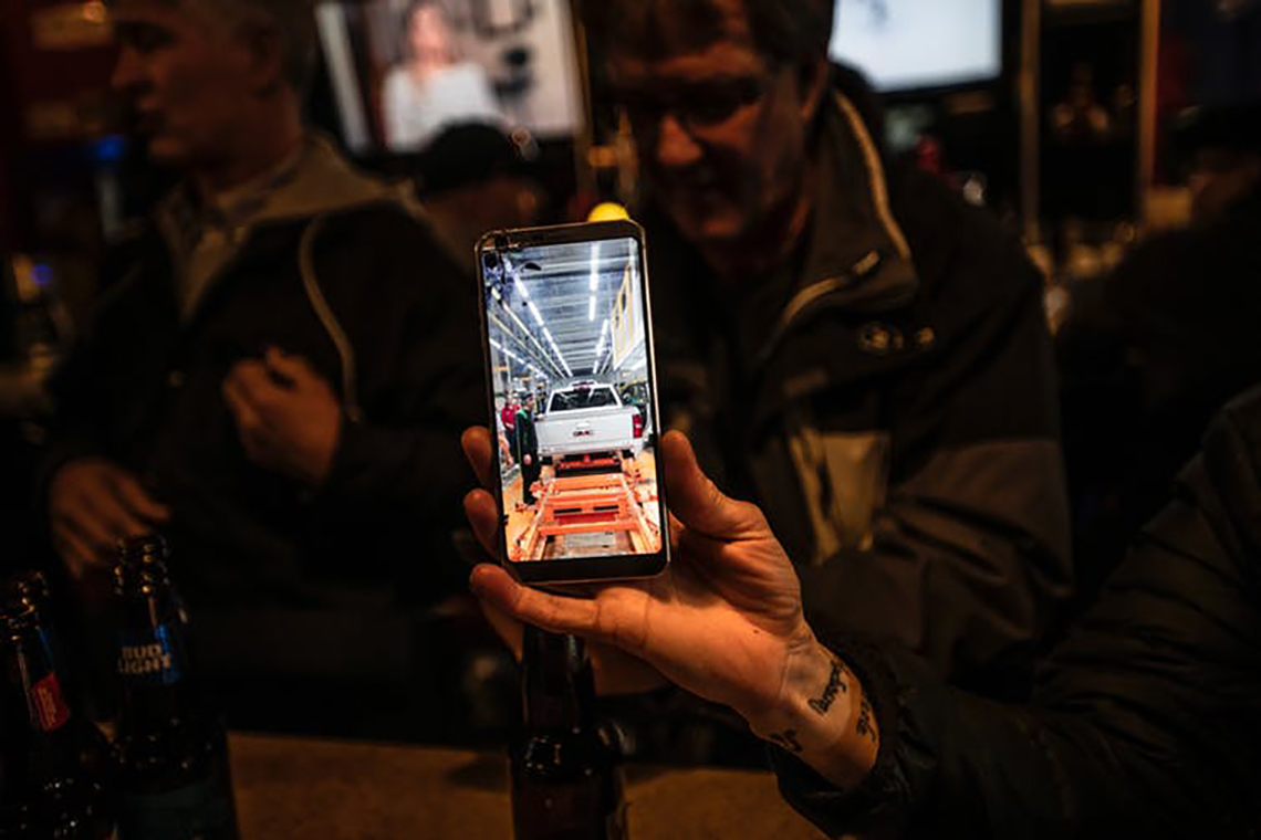 Photo of a GM worker holding an iPhone with a picture of a truck on the Oshawa plant's assembly line