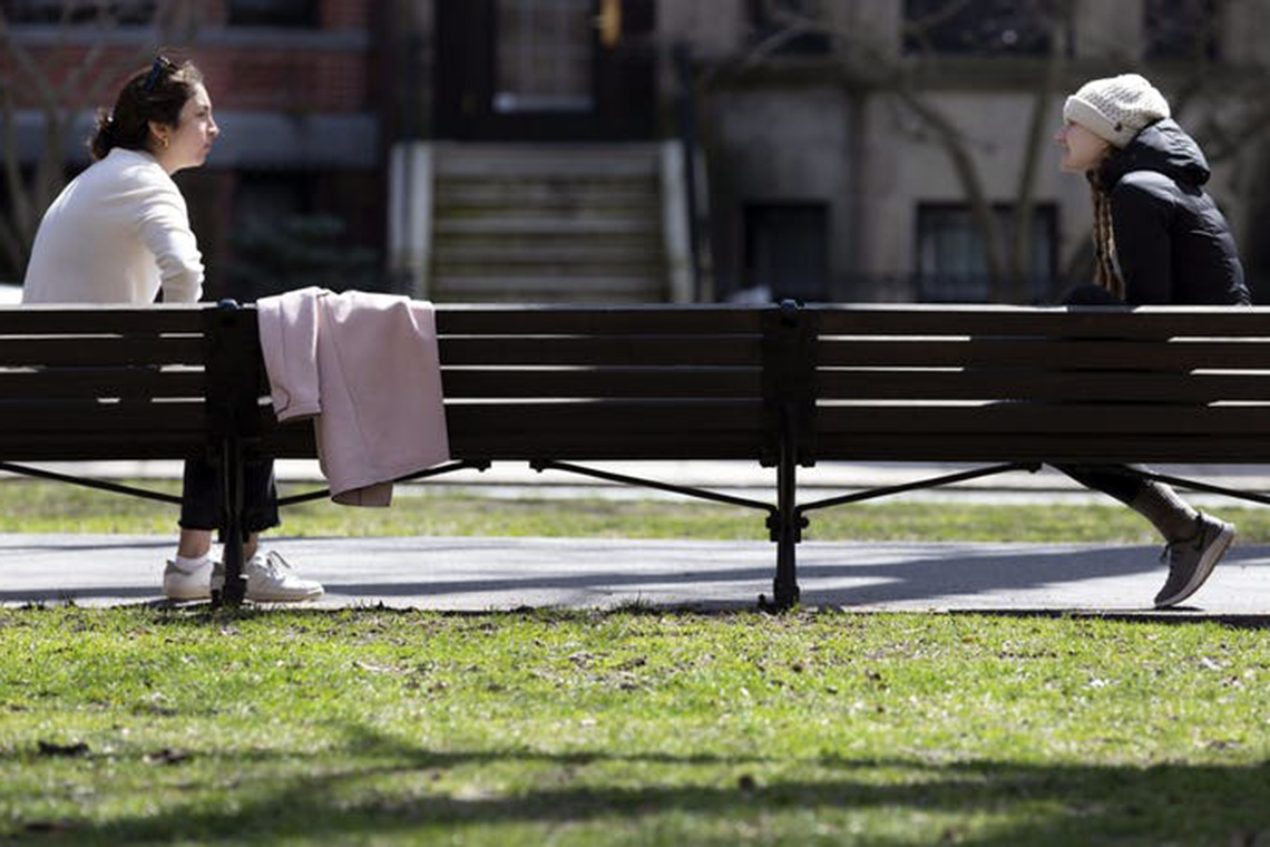 Two people on park benches separated by a distance of about 7 feet