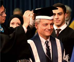 President Meric Gertler having new cap put on him at installation ceremony