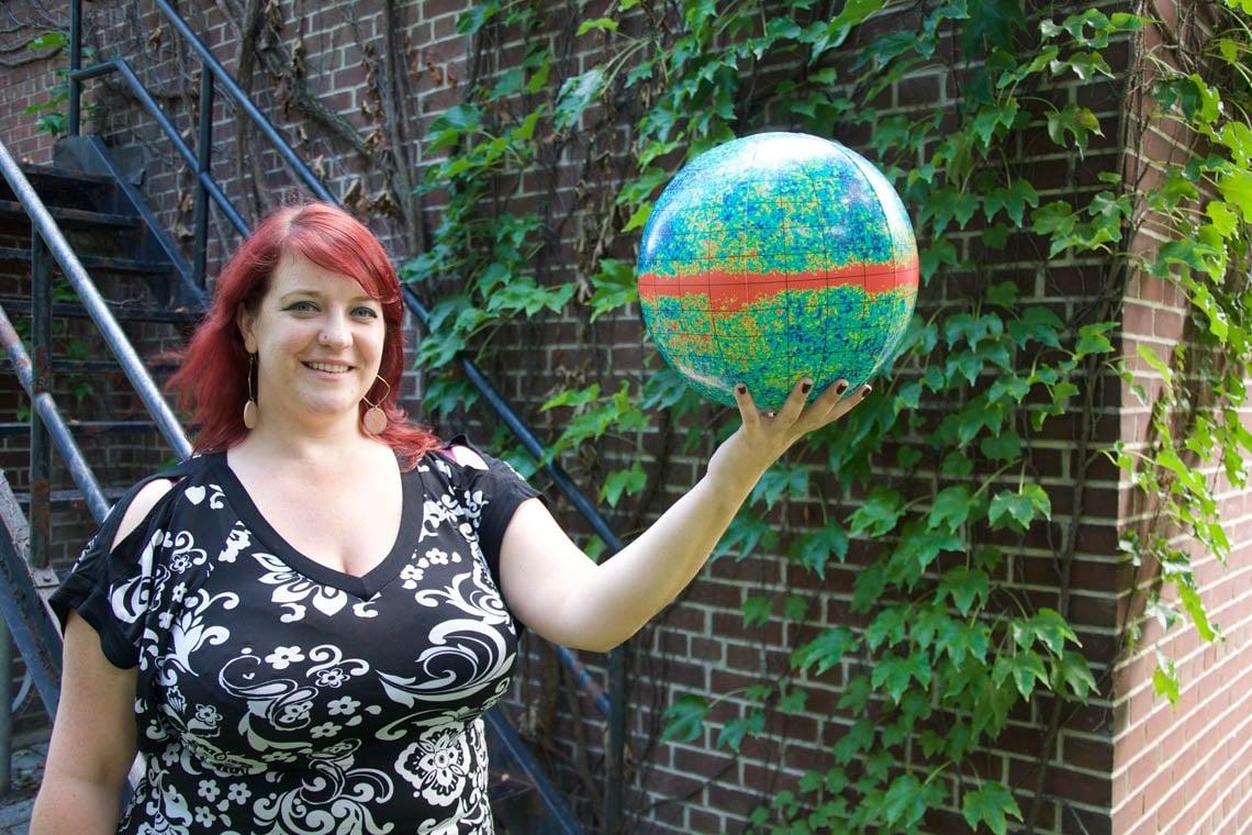Renée Hložek holding a globe