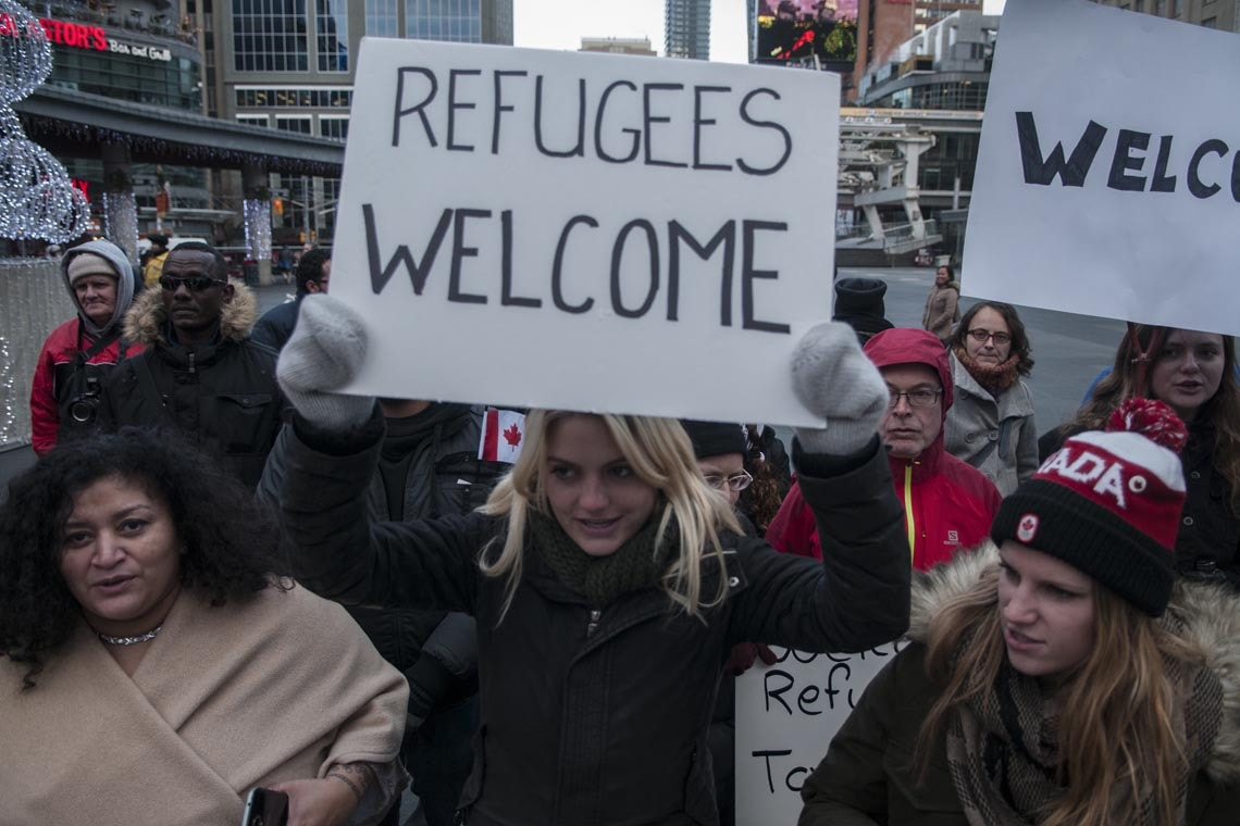 "Woman holding a sign saying ""Refugees Welcome"" at rally in Toronto"