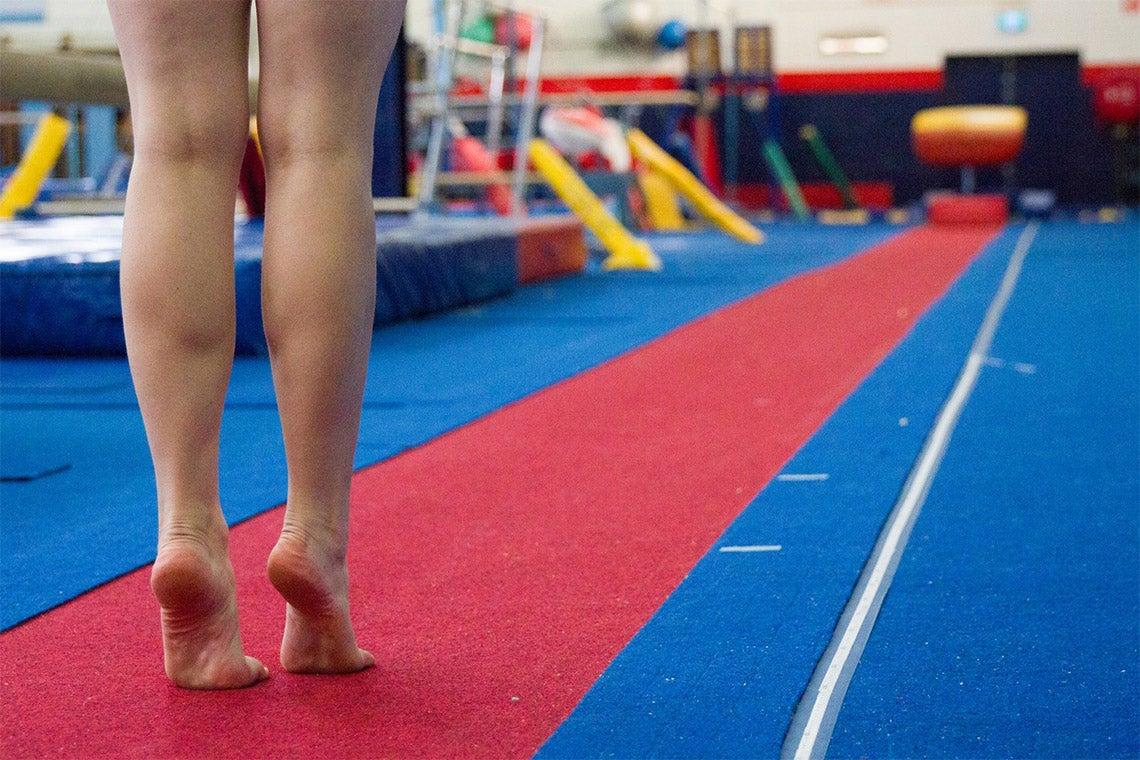 A female gymnast trains in a gym