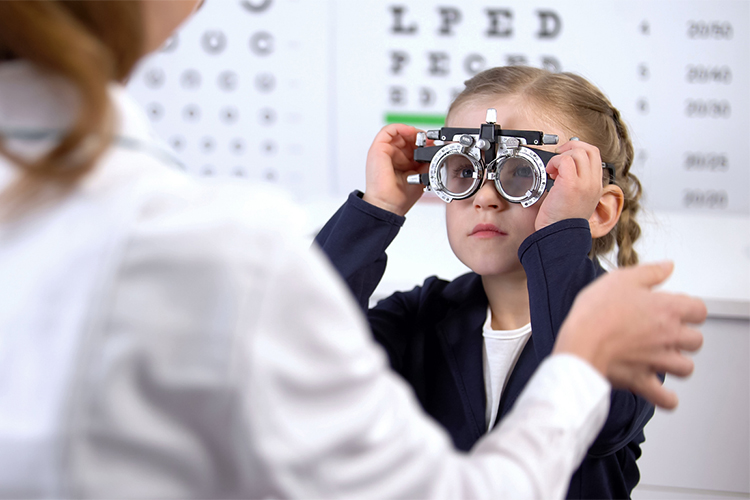 a young girl, about age 6, taking an eye exam