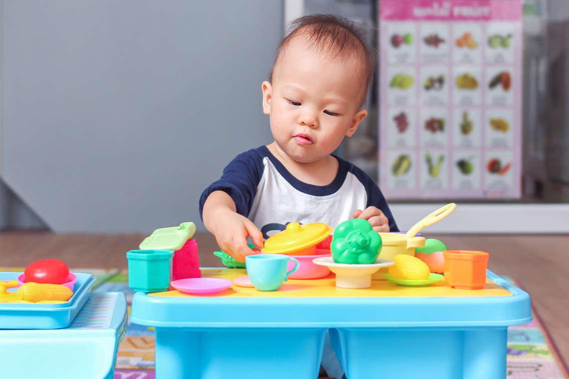 A young asian boy plays with colourful plastic toys
