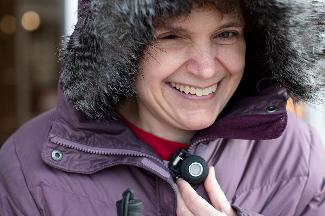 A woman with one eye smiles as she holds her BuzzClip, an iMerciv assistive technology device for safer walking
